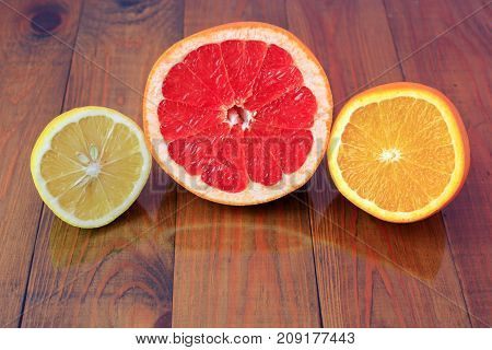 cut grapefruit orange and lemon are reflected on the wooden surface. Juicy citrus fruits