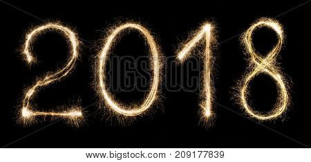 Shining 2018 numbers. New year symbol written with sparklers at black isolated background