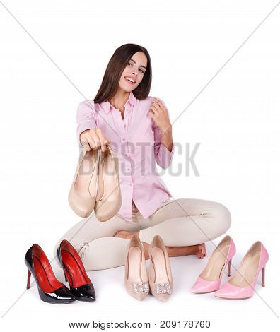 A beautiful girl with dark long hair holds a pair of beige shoe heels in her hands. Three pairs of high-heeled patent shoes isolated on a white background. Close-up of shoes. Fashion concept.