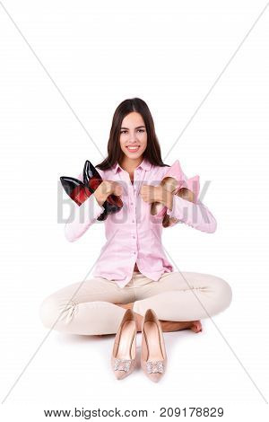A beautiful girl with dark long hair holds a pair of heels in hands. Three pairs of high-heeled patent shoes isolated on a white background. Close-up of shoes. Fashion concept.