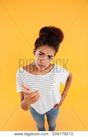 Top view of young african puzzled displeased lady looking up at camera with folded hands isolated