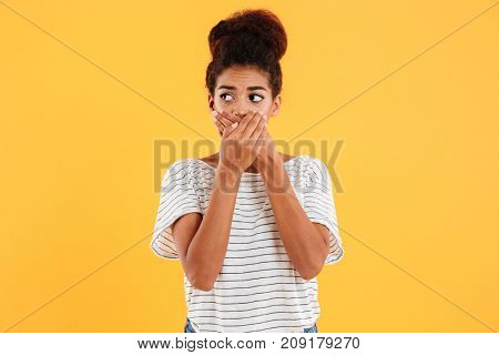 Young nervous african woman covering her mouth and looking aside isolated over yellow