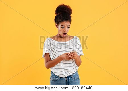 Shocked african lady with curly hair using and typing smartphone isolated over yellow