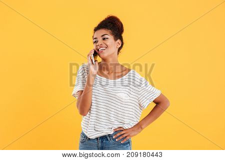 Cheerful positive african woman talking on phone while standing isolated