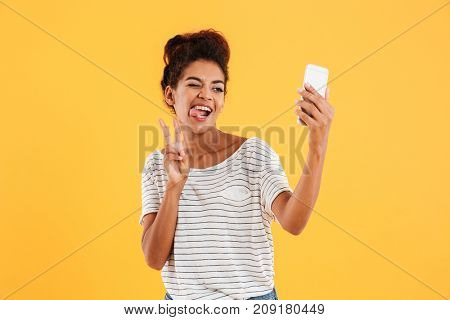 Young funny african casual lady grimacing and making selfie on smartphone isolated over yellow