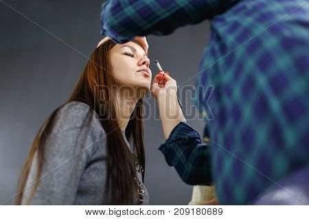 The make-up artist is applying makeup to the young girl. In the studio on a black background. Bottom view.