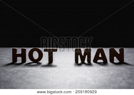 Words Hot Man Of Wooden Letters On A Dark Texture With A Black Background With Backlight. Lighting E