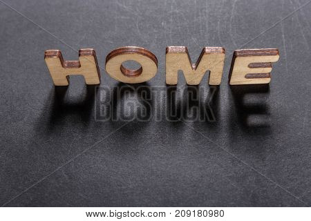 Word Home Of Wooden Letters On A Dark Texture With A Black Background With Backlight. Lighting Effec