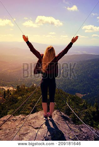Girl on rock. Tourist on the top of Grosser Arber mountain in National park Bayerische Wald, Germany.