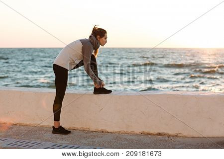 Portrait of young slim sport woman tying shoelace at the morning seaside