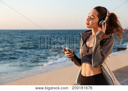 Close-up portrait of cheerful young sport woman listening to music with closed eyes on seaside