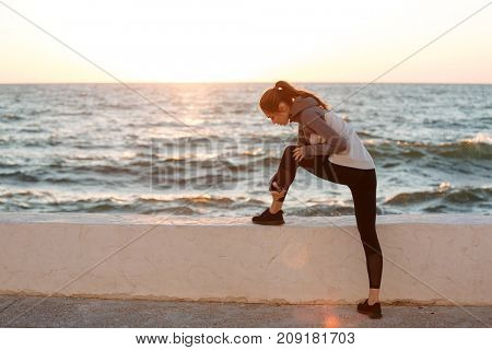 Photo of young slim sport woman tying shoelace at the seaside