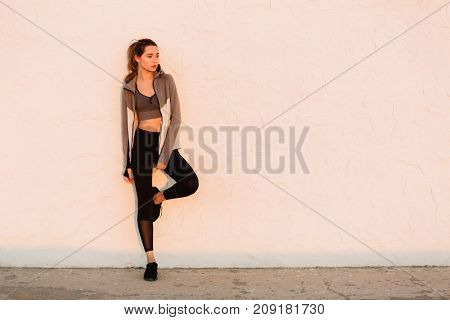 Young beautiful sport woman resting after running near white wall, looking at sunrise