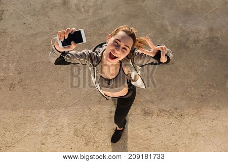 Top view of funny brunette sport woman showing peace sign while listening to music, looking at camera