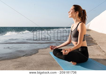 Portrait of cheerful brunette in sportwear sitting in lotos pose while practicing meditation at seaside
