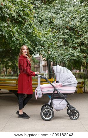 Happy young mommy spend time with a little baby in baby carriage in the park outdoors. A pretty woman posing at camera on the nature background. Full lenght of woman. Family concept.