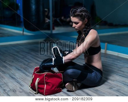 Young fighter boxer girl preparing for training. She puts on boxing gloves sitting on the floor of gym. Fit girl