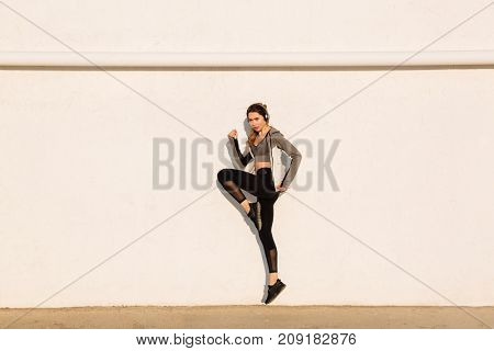 Full length photo of young sport woman jumping near white wall
