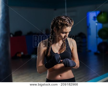 Young fighter boxer girl wearing hand bandage  during training in gym.