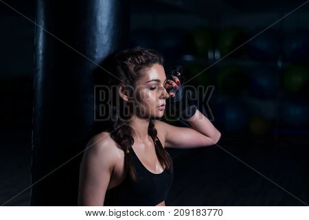 Upset young fighter boxer girl wearing boxing gloves, standing in dark gym near punching bag after loosing fight. She coveres her face with hand.