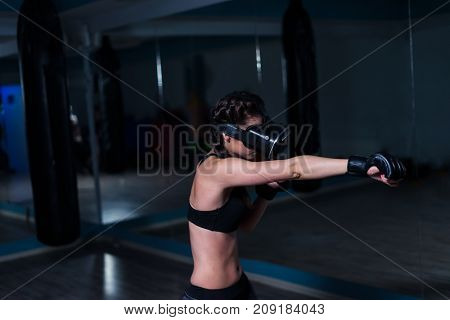 Young fighter boxer fit girl in VR glasses wearing boxing gloves in training in additional reality. Boxing game in virtual reality 360 degrees. Futuristic gaming