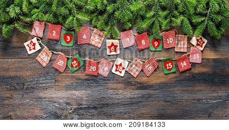 Advent calendar with Christmas tree branches on dark wooden background