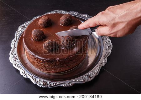 A man's hand with a kitchen knife above a chocolate homemade biscuit cake on a metal plate