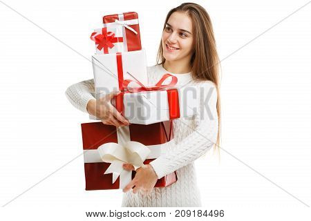Beautiful smiling girl with a long hair posing on the camera in studio and holding christmas gift isolated on white background. Close-up of gifts. Holiday concept.