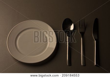 Empty plate with spoon, knife and fork. low key minimalistic picture