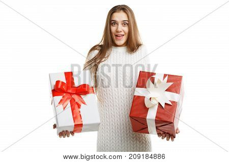 Pretty cutie girl with a long hair posing on the camera in studio and holding christmas gift isolated on white background. Close-up of gifts. Holiday concept.