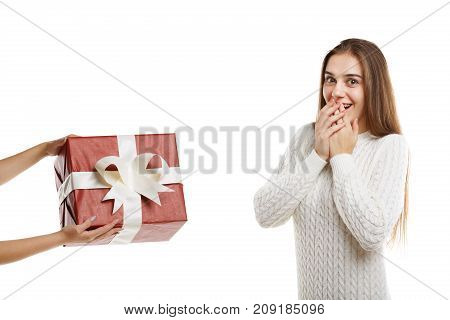 Wow An excited young cute girl receives a gift. It is red with a white ribbon. Girl dressed in white clothes, isolated on white background.