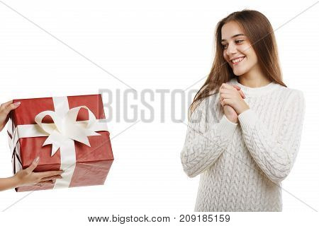 Wow. An excited young cute girl receives a gift. It is red with a white ribbon. Girl dressed in white clothes, isolated on white background.