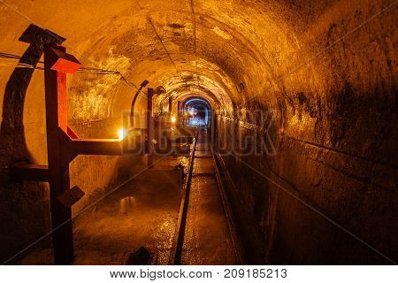 Abandoned round underground technical mine tunnel with a narrow-gauge railway