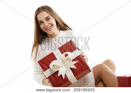 Young girl with a red gift and a white ribbon, isolated on white background. The concept of a holiday. Close-up.