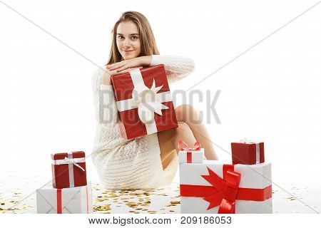Young girl with gifts isolated on white background. Sits on the floor with confetti. The concept of a holiday. In full growth.