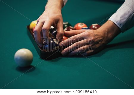 Playing billiard. Billiards balls on green billiards table. Caucasian player put ball inside. View from side. Billiard sport concept. Pool billiard game.