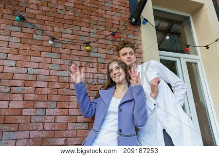 Funny young fashionable couple of romantic modern girlfriend and confident young man posing on a brick wall background. Copy space.