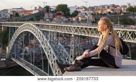 Young woman with blond dreadlocks on viewing platform opposite the Dom Luis I bridge across Douro river in Porto, Portugal.