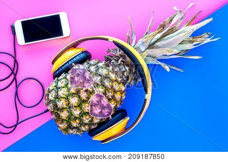 Stylish pineapple in sunglasses listen to music on the smartphone on blue and pink background top view.