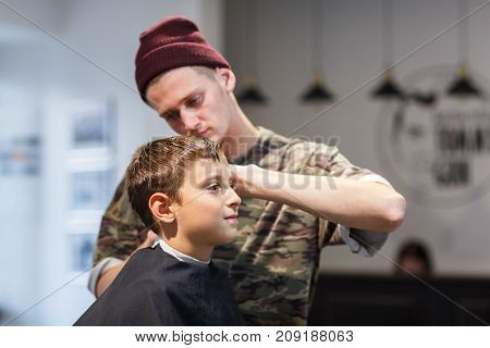 Hairdresser short-cropped in a brown hat in a barbershop makes a haircut for a young guy