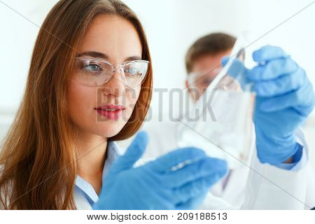 Female technician arms in protective gloves hold fluid sample bottle portrait. Medical worker in uniform use reagent tube, virus infection exam, biological toxic reaction, drug creation concept
