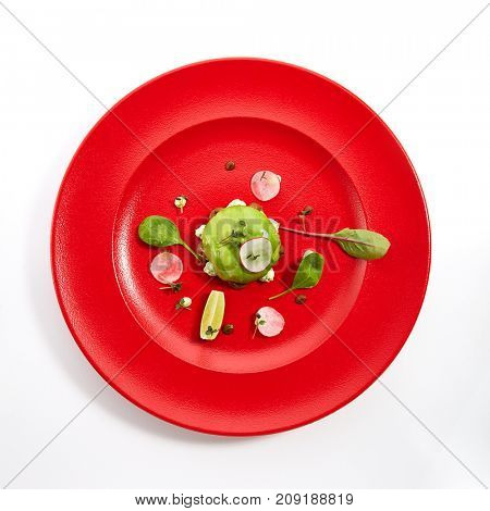 Pan-Asian menu in restaurant - dish called Kamchatka ball - crab inside outside avocado with fruit and vegetable slices sprinkled with fresh herbs on red plate. Top View