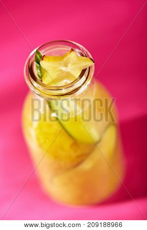 Summer Lemonade Cocktail - Tropical Orange Lemonade with Cucumber. Lemonade Glass Bottle on Bright Magenta Background.