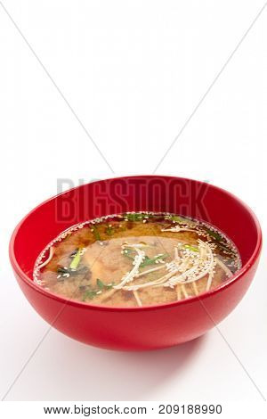 Classic miso soup with sprinkled greens and sesame seeds in red bowl. Menu in  Asian restaurant