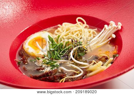 Ramen soup with pork - Japanese soup with wheat noodles with mushrooms slice of boiled chicken egg sprinkled with fresh herbs and sesame seeds in red bowl. Menu of Asian restaurant