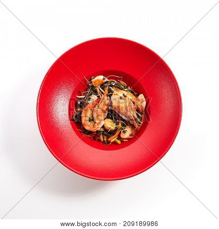 Pan-Asian restaurant. Noodles with cuttlefish ink, shrimps and salmon with slices of vegetables sprinkled with fresh herbs in red plate. Top View
