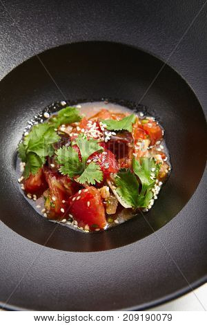 Pan-Asian menu in  restaurant. Eggplant in Asian style with the addition of tomato sesame and fresh herbs in an iron bowl.