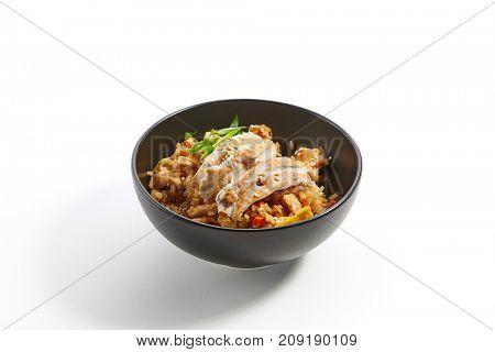 Fried rice with chicken vegetables fresh herbs and seasonings in dark bowl. Pan-Asian cuisine in restaurant