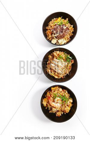 Teppanyaki Fried rice with chicken shrimp beef vegetables fresh herbs and seasonings in dark bowl on white isolated background. Pan-Asian cuisine in restaurant. Top View