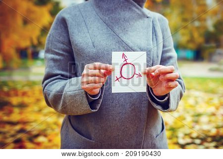 young Caucasian woman in autumn park showing piece of paper with transgender symbol drawn in it. Human rights day concept